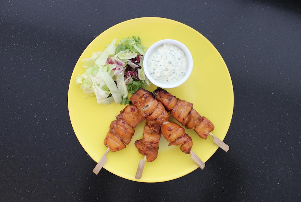 Pittige kipspiesjes op bord met saus en salade