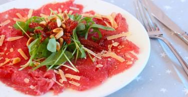 Rundercarpaccio met rucola, zongedroogde tomaat en pijnboompitten